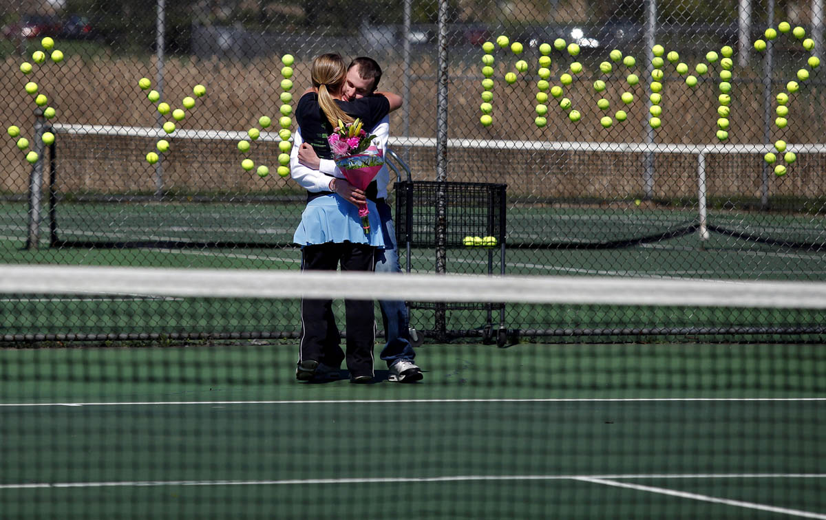 Kalamazoo Christian senior Jared Dykstra, 18, hugs senior Sydney Batts, 17, after surprising her with flowers and asking to go to the junior/senior prom before the start of Batts' tennis practice Friday afternoon. {quote}I thought using the tennis balls was very unique,{quote} said Batts. {quote}It was very cute and better than what I was expecting.{quote} The couple have been dating for a month.