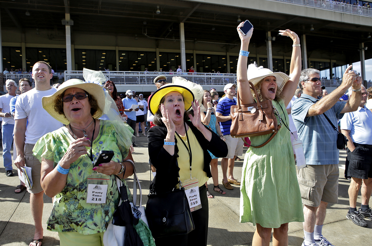 Nardeen Henderson, left, Debra Thurston, center, Debi Postma, right, all of Smithfield cheer on their horses in excitement during an early race of the Virginia Derby at Colonial Downs.