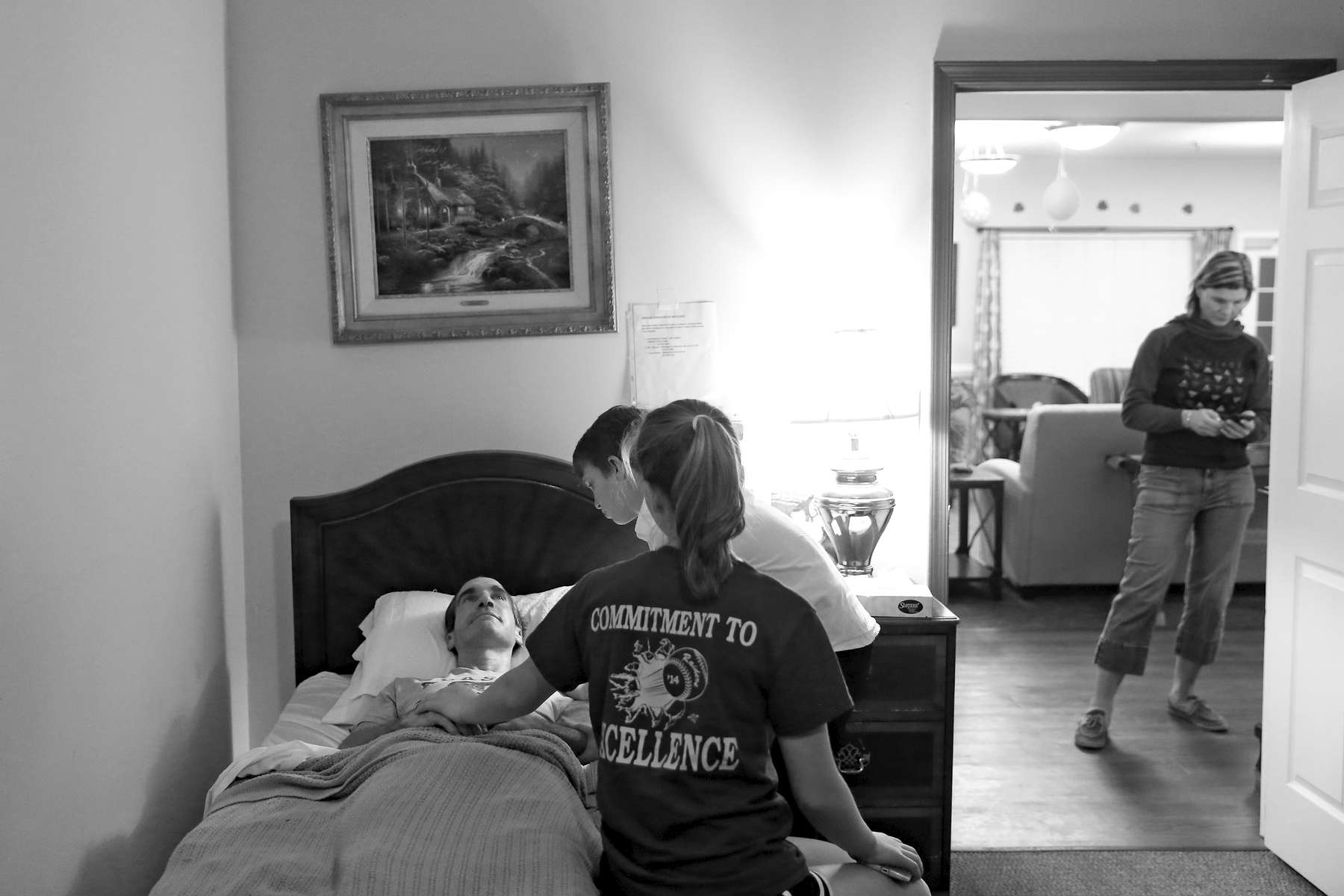 Bradley Garner, center, and Frankie Garner stand beside their father, Jim Garner, while he lays in bed at Commonwealth Assisted Living in Hampton as Karen Garner responds to messages on her phone Thursday evening March 24, 2016. Jim died from Alzheimer's April 2, 2016. Jim was diagnosed by the National Institute of Health in 2011 with {quote}mild cognitive impairment,{quote} the precursor to early-onset Alzheimer's disease. The genetically pre-determined disease has devastated his family--his mother died of the disease at age 61, his older brother at 52.