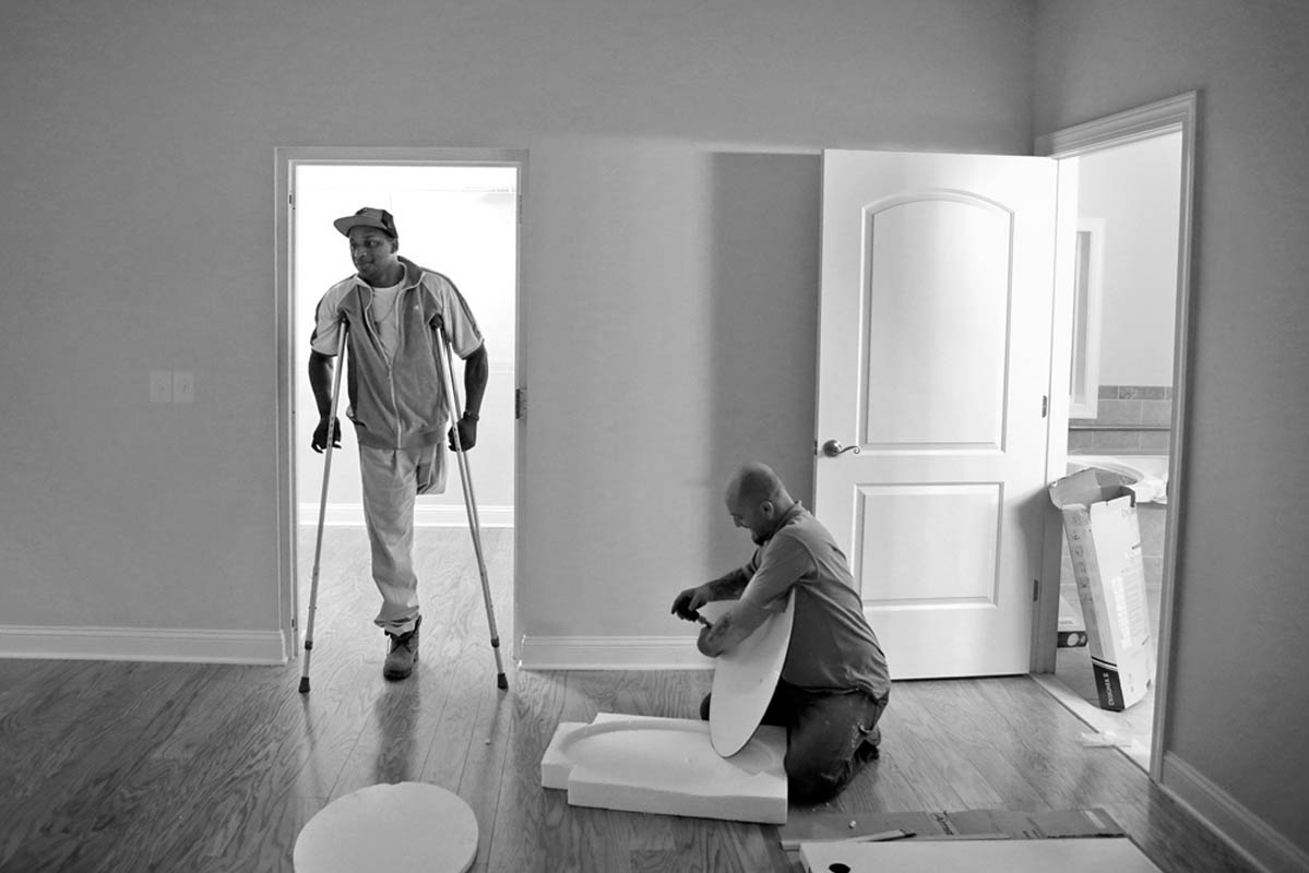Johnathan Jackson, left, talks with Tom Thorpe as he completes the finishing touches on the master bedroom inside Jackson's newly built home. Jackson lost his leg in Afghanistan after doctors say he was exposed to an unknown toxin. Homes for Our Troops built Jackson a house and he takes the keys to the new home on Friday.