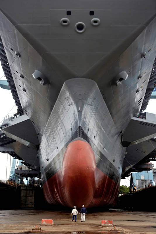 Media tour beneath the bow of the carrier Gerald Ford as it sits in Newport News Shipbuilding's dry dock before water is released for the first time flooding the dock.