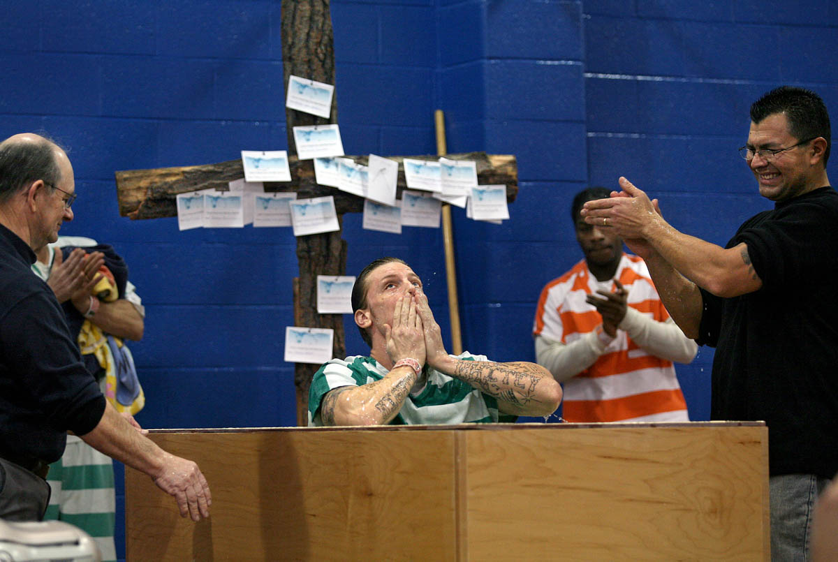John Vincent Grogan III, center, looks to the heavens after being baptized by St. Joseph County Jail chaplain Jake Schwartz, left, and Three Rivers' Riverside Church assistant pastor Jerry Solis, right, during a full immersion baptism of inmates at the St. Joseph County Jail in Centreville Thursday morning. The baptism was through the church's Christ Center Celebrate Recovery program.