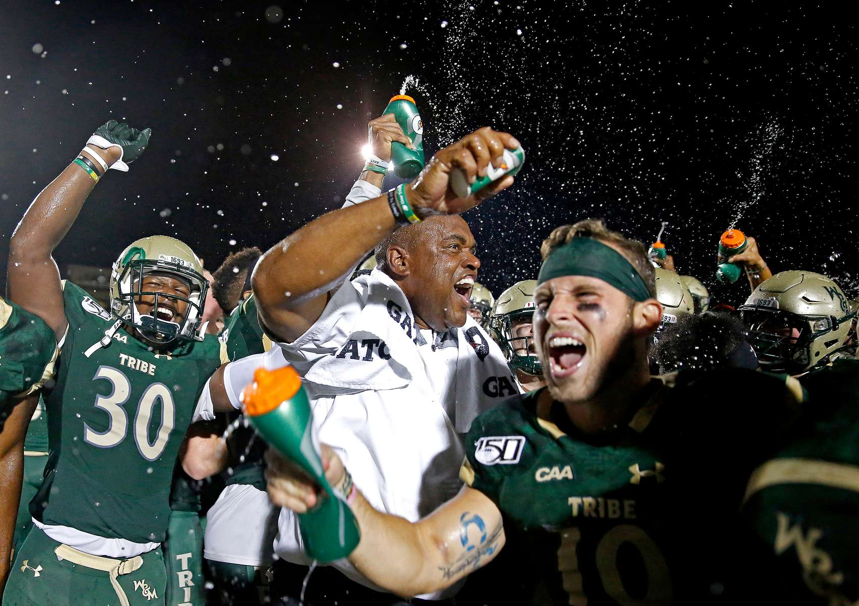 William and Mary head football coach Mike London, center, celebrates with his players after defeating Lafayette 30-17 during Saturday's football game at Zable Stadium August 31, 2019.