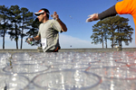 A runner grabs a glass of water from a volunteer at the Lions Bridge during the One City Marathon in Newport News Sunday morning.