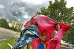 Jacquela Wynn, left, Zyion Jones, center, and Serenity Jones attempt to take cover underneath a blanket as high winds, rain and storm clouds approach Huntington Beach.