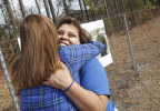Third Place | General NewsJOHN ALTHOUSE, THE DAILY NEWSThrilled with the soon arrival of their husbands, April Colley (L) of Portsmouth, OH receives a hug from Yhesly Anaya (R) of Cleveland, OH along Highway 24E near the main gate entrance to Camp Lejeune, Jacksonville where they just hung welcome home banners for their husbands LCpl Roy Colley and LCpl Pedro Anaya, Jr. respectively.  The image of LCpl Pedro Anaya, Jr. is visible on the banner in the background.