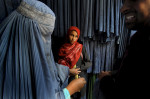 HM | FeatureSara DavisFreelanceSakara, 12, keeps a skeptical eye on a burqa dealer as her mother, Nasreen, negotiates the price of a new burqa at a burqa shop in Kabul, Afghanistan.