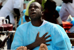 Second Place | News Picture StoryChuck LiddyNews and Observer Bourdeau M'etellus sings a hymn as he waits outside on his hospital bed after a 6.1 earthquake cause all the buildings in a hospital complex in Port Au Prince be evacuated.