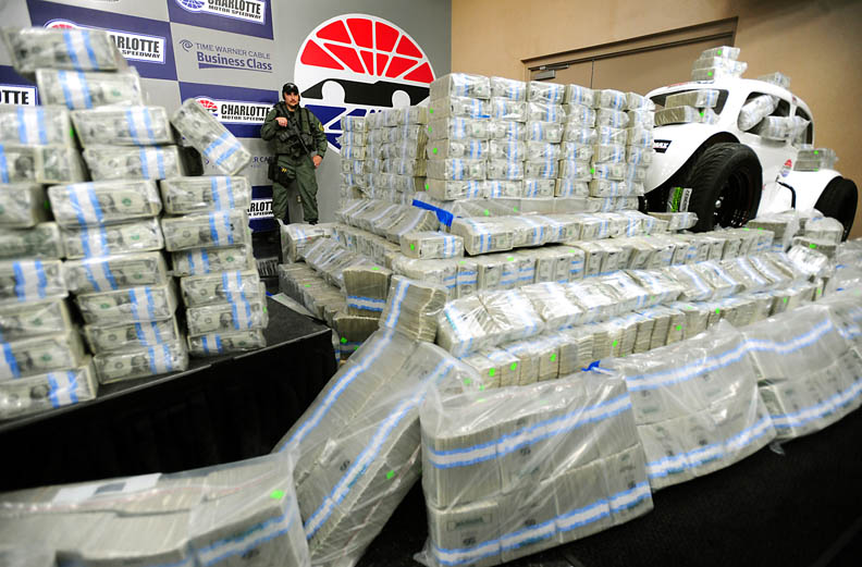 Second Place | Sports Story Jeff SinerCharlotte ObserverA armed guard closely watches wrapped stacks of $1. bills totally one million dollars that represented the total purse for a Legends race.