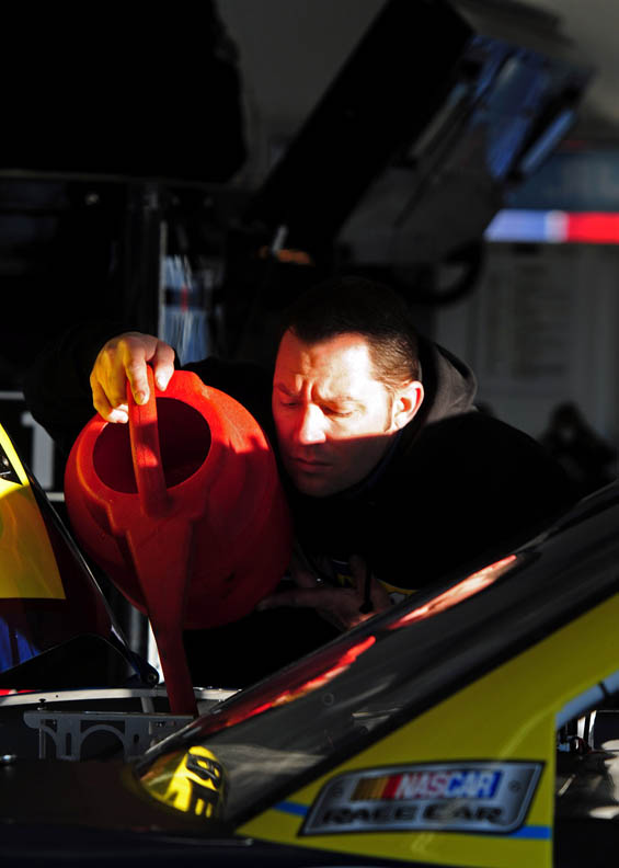 Second Place | Sports Story Jeff SinerCharlotte ObserverA shaft of early morning light highlights a crewman as he carefully pours liquid into an engine.