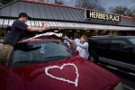 First Place, Photo StoryJerry Wolford, News-RecordFriends decorate the wedding couple's car after their wedding ceremony outside Herbie Place restaurant.