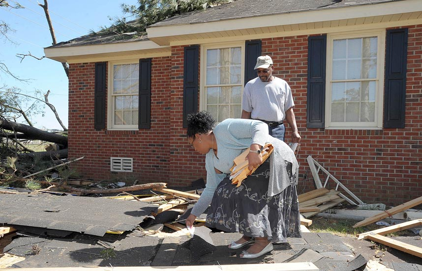 Second Place | Photo StoryBrad Coville, The Wilson TimesDawn Ellis, and Jimmie Rogers sift through debris in front of their home located in the 100 block of Plaza Drive Sunday afternoon after a tornado tore through their neighborhood Saturday.