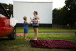 First Place | Photo StoryJames Robinson, Fayetteville ObserverShannon Lenderman talks to Autumn McPhearson, 7, while holding her son Joel Johnson before the movie at Badin Road Drive-In Friday night.