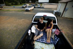 First Place | Photo StoryJames Robinson, Fayetteville ObserverJesse Strange and his fiance Brittany Williams sit in the back of Strange's truck waiting for the movie to start at Badin Road Drive-In Friday night.