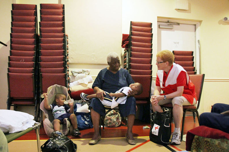 Second Place | General NewsEmma Tannenbaum, Rocky Mount TelegramFlorence Topping, center, talks with Red Cross Volunteer Eilene Guy, right, on Firday about her evacuation with her great grandchildren, My'Mir Morris, 2, left, Tyler Morris, 2, sleeping, and Miricha Morris, who will be three on Sunday, not pictured.  Tyler and Miricha are brother and sister, My'Mir is their cousin.  They evacuated from Swan Quarter, NC and arrived at Englewood Baptist Church in Rocky Mount, NC, around 7pm Thursday night, which has been converted to a shelter for evacuees fleeing Hurricane Irene.