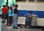 Third Place | FeatureTodd Sumlin, The Charlotte Observer8/25/2011 An older student drops to his knees to get a drink of water at Berryhill School in west Charlotte Thursday morning. The school was previously an elementary school but now has pre-k through 8th grade students.