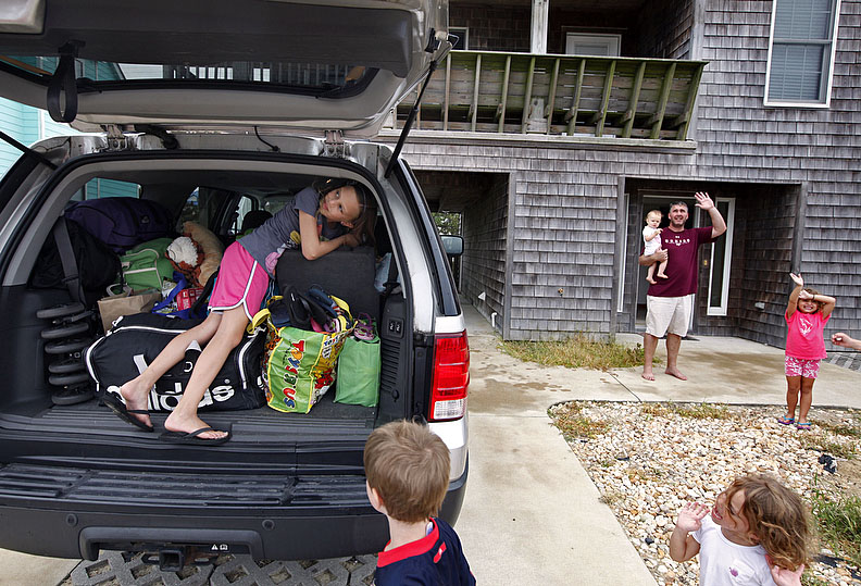First Place | Photo StoryShawn Rocco, News & ObserverElla Clark, left, and her family look up and wave at the news helicopters circling Nags Head as her family prepares to leave before Hurricane Irene hits on Friday, August 26, 2011. The Clarks own the house but live in Virginia and were cutting their vacation a few days short to head back home. With four young children they didn't want to take the risk of staying and then deal with the possibility of no water or power.