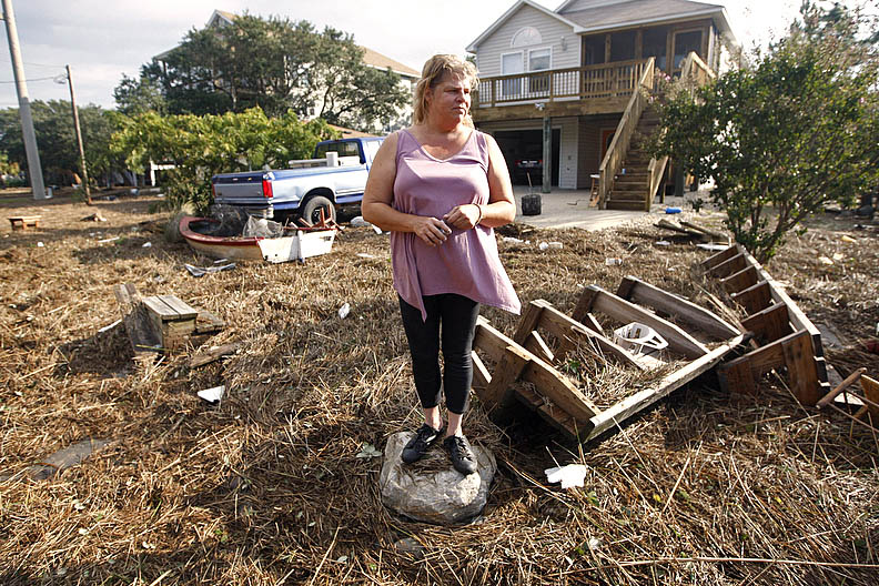 First Place | Photo StoryShawn Rocco, News & ObserverShari Compton looks at the devastation on Bay Drive in Kill Devil Hills on Sunday, August 28, 2011. Debris from the Albemarle Sound covers the street after overflowing on Saturday night into Sunday morning. With Hurricane Irene gone the clean up begins.
