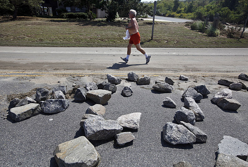 First Place | Photo StoryShawn Rocco, News & ObserverGordon Kimple jogs past stones from a breakwall that broke and washed up onto N.C. 12 in Duck.