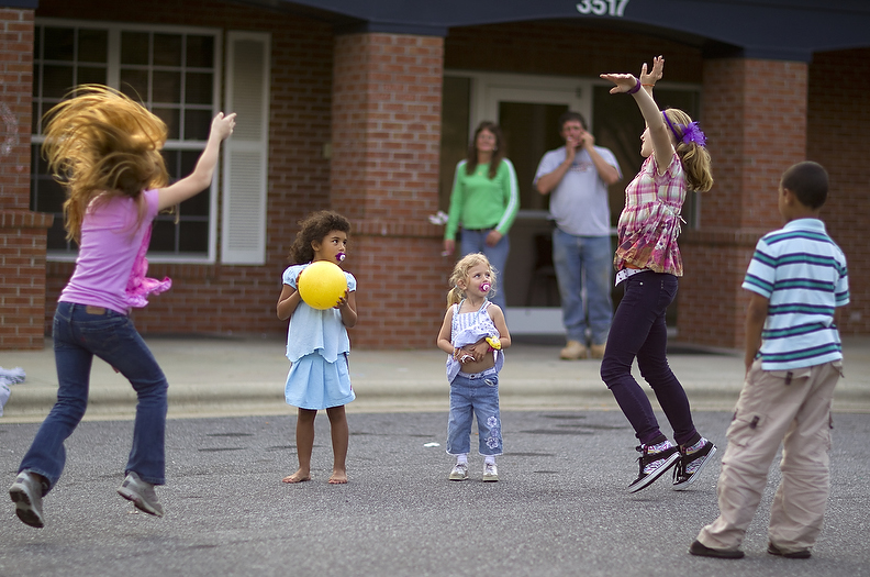 Second Place | Photo StoryJerry Wolford, News-RecordThe children play in front of the Pathways' building, a shelter for homeless families.The Tucker family live at The Pathways Center, a housing program of the Greensboro Urban Ministry. The family consist of Kevin Tucker (42), Carol Tucker (46) and children Amanda Tucker (13), Sarah Grace Tucker (11), Bradley Tucker (9), Olivia Tucker (6) and Chelsi Tucker (3).