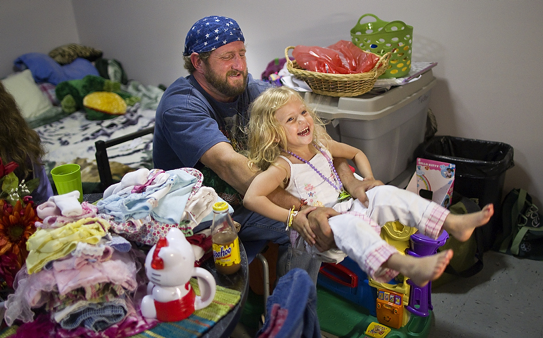 Second Place | Photo StoryJerry Wolford, News-RecordKevin Tucker entertains Chelsi, 3, by swinging her with his arms.