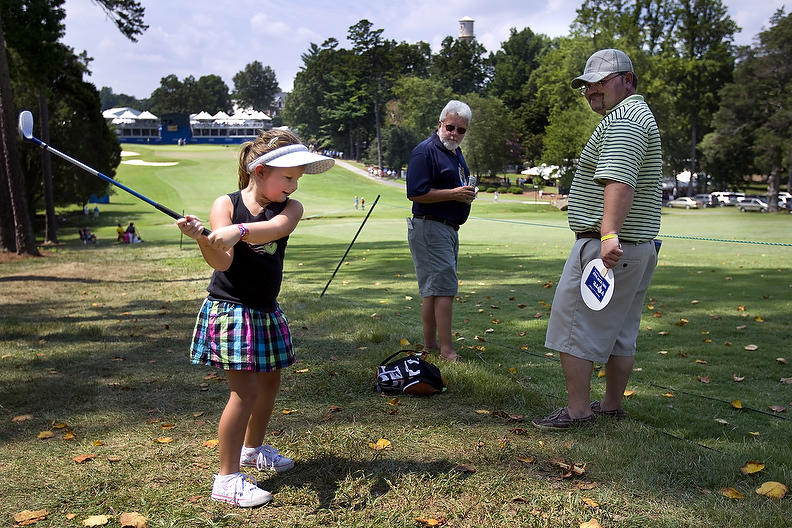 Third Place | Photo StoryJerry Wolford, News-RecordReagan Nichols, 5, swings her junior club along the eighteenth fairway while waiting for the next group of golfers with her father, Jamey Nichols, and grandfather, Jimmy Nichols.
