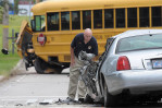 Third Place | Spot NewsBrad Coville, The Wilson Times09/19/2011 - A Wilson Police Detective inspects a car that collided with a Wilson County School bus Monday September 19, 2011 as it was taking students to Fike High School. No students were injured in the crash that killed the driver of the Lincoln.