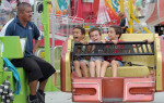 Honorable Mention | FeatureBrad Coville, The Wilson Times09/24/2011 - A carnival worker keeps an eye on Tyson Arrington (7), Dylan Smith (7), and Hunter Smith (8) Saturday afternoon at the Wilson County Fair. Officials say attendance was down because of several days of rain throughout the week long event.