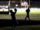 Second Place | Photo StoryJerry Wolford, News-RecordChildren play in the shadows of the stadium.