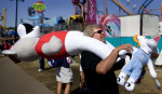 Third Place | Photo StoryJerry Wolford, News-RecordStacey Whitfield, of Hobgood, NC, watches his daughter on a ride while keeping up with prizes won at the fair. Whitfield, a Duke fan, is carrying stuffed mascots of NCSU and UNC Chapel Hill, at the NC State Fair.