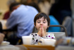 First Place | General NewsJerry Wolford, News-RecordAlexa Bird, 5, during a prayer during the Greensboro Urban Ministry's 20th annual Feast of Caring soup dinner to raise money for area food banks.