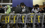 First Place | Photo StoryShawn Rocco, News & ObserverAt 11:40 p.m. Lateefah Sanders waits in line for the midnight opening of Best Buy on Capital Boulevard in Raleigh on Black Friday, November 25, 2011. She and a friend had been waiting since 6:30 p.m. on Wednesday to buy flat-screen televisions that were on sale for $200. {quote}I'm tired and it's been a long time, but both of us will be saving over $1000,{quote} she said.