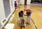 Second Place | Photo StoryGray Whitley, The Wilson Times11.3.2011 - Malik Morris, a deaf/blind student, places his head in the crook of his arm during P.E. class as intervenor Krystal Cooper patiently tries to get his attention for the next dodgeball game at the Eastern North Carolina School for the Deaf. The action blocks out the gyms's bright lights so Malik feels the action protects his eyes.