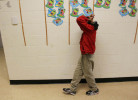 Second Place | Photo StoryGray Whitley, The Wilson Times11.3.2011 - Malik Morris, a deaf/blind student, walks along the edge of the school's hallway after lunch at the Eastern North Carolina School for the Deaf. He often puts his head in his arm to help him balance, blocking the light out of his eyes. {quote}He's trying to focus on where he is going,{quote} said Krystal Cooper, Malik's deaf/blind intervenor. {quote}He gets support from the wall.{quote}