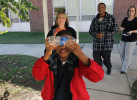 Second Place | Photo StoryGray Whitley, The Wilson Times11.3.2011 - Malik Morris, a deaf/blind student at the Eastern North Carolina School for the Deaf, is fascinated by the view through a water bottle as he walks to class with his intervenor Krystal Cooper. He often holds a water bottle close to his eyes to see different colors and textures. The activity is a simple way of Malik relating to his environment.