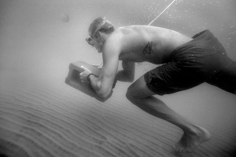 Third Place | Sports Photo StoryLogan Mock-BuntingJake Drahos runs sprints underwater - past a jellyfish - while carrying a cement block. The exercise conditions the body to be more comfortable with low levels of oxygen underwater, but is also a mental challenge. During such a drill there are at least two spotters watching the participant. ltqmb