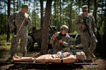 POY, Runner UpAndrew Craft, Fayetteville Observer Spc. David Kerr, left to right, Staff Sgt. Thomas Sager and Spc. Christopher Robinson look down at a dummy after attaching it to a stretcher during the Army Medical Command's best warrior competition at the Medical Simulation Training Center on Fort Bragg, N.C.