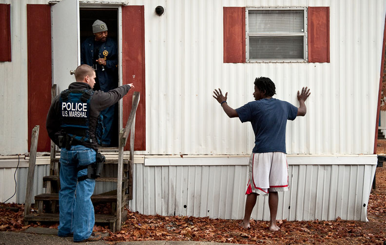 POY, Runner UpAndrew Craft, Fayetteville Observer A resident stands outside as U.S. Marshals, Brandon Taylor and Will Britton, look for James Harvey during operation Urban Shield. Harvey is wanted on kidnapping and other charges. Harvey was not at the home.