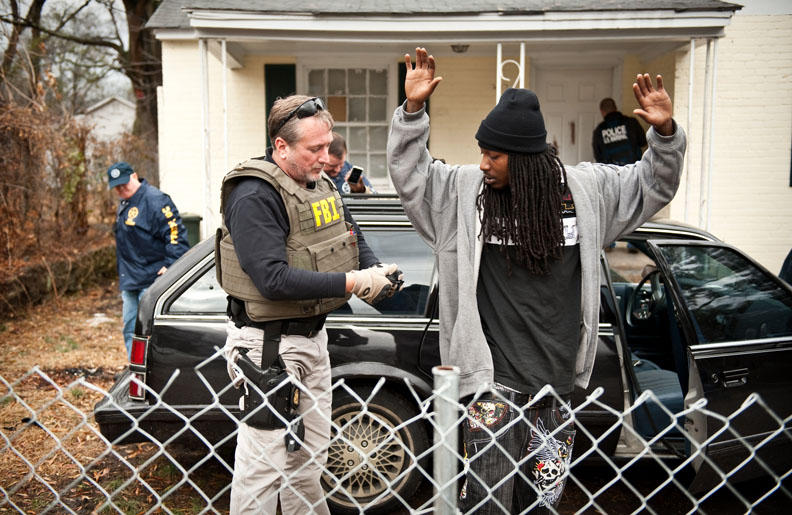 POY, Runner UpAndrew Craft, Fayetteville Observer FBI agent Tim Gannon, left, searches a man while looking for Mario Brown at a home on Nimocks Lane during operation Urban Shield. Brown had been spotted earlier in the day riding in the black station wagon.