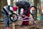 Second Place | Photo StoryJerry Wolford, News-RecordStephen Bartley, 13, works with Tymier Starks, 11, as they work at building Tymier a bicycle.