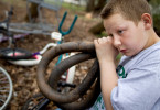 Second Place | Photo StoryJerry Wolford, News-RecordKenneth Pedley, 13, at work testing bicycle tire inner tubes. The boys pump up multiple tubes and pick the one that leaks the least.