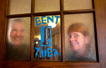 Honorable Mention | PortraitJerry Wolford, News & RecordNicki Deyton (left) and Tracy Hart behind the frosted glass of the door to Bent Tuba Studio.