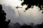 Third Place | Spot NewsMike Spencer, The Wilmington Star-NewsA helicopter carries a bucket of water over a brush fire along 17th Street near the Cameron Art Museum Monday April 16, 2012.JUDGES COMMENTS: Layering helps differentiate standard brush fire coverage. Just a pretty shot.