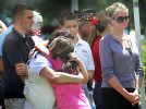 Third Place | Spot NewsChuck Beckley, Daily News      Patricia Desens and her daughter, Somer, hug after hearing their son/brother's name , Spc. Daniel Desens, read during bell ceremony Monday morning at the Coastal Carolina Veterans Cemetery Memorial Day Service.JUDGES COMMENTS: A touching image although a bit hard to read. Background is too busy and hurts the overall impact of the photo.
