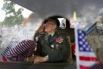 First Place | PortraitJerry Wolford, News & RecordWorld War II Veteran Curry Regan receives a kiss from Peggy Owen as he sits in a Jeep before the start of the parade of a Memorial Day Parade.The two worked together for several years in a local bank. JUDGES COMMENTS: Beautiful image caught in a unique way. We loved the way the shadow framed the vet and all the details throughout the frame, such as the clutching of hands and the flag. Nice work by the photographer to move away from your typical parade shot and try something different.
