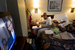 Second Place | General NewsJerry Wolford, News & RecordMable Scott takes notes during President Barack Obama's health care address as she cares for her sick husband, Moses Scott, in their single room studio apartment at the Suburban Extended Inn while he is treated for cancer. The US Supreme Court handed President Obama a major victory by upholding the sweeping 2010 healthcare law. Moses Scott has bone and thyroid cancer and has been under Hospice care for three weeks.