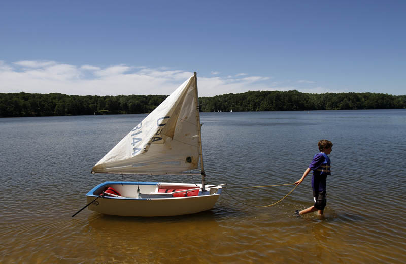 Third Place | FeatureChris Seward, The News and ObserverSpencer FoxDavis (cq), 12, from Raleigh hauls his sailboat after coming to shore during a youth sailing class held at Lake Wheeler in Raleigh, NC on JUne 26, 2012.  Tuesday offered Triangle residents an unseasonably cool clear day with low humidity and highs only in the 80's.  Enjoy it, as forecasters are calling for temperatures near 100 degrees later this week.