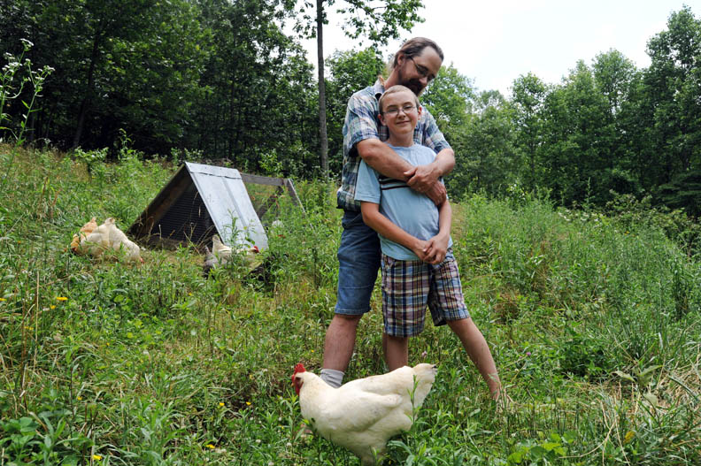 First Place | PortraitErin Brethauer, The Citizen-TimesWalt Harrill hugs his son, Andy, on their family's farm Wednesday.  Harrill and his wife, Wendy, run Imladris Farm in Fairview which produces berries, jams, produce and rabbits.  The couple home schools Andy who takes care of the farm's chickens.