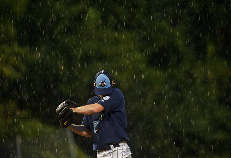 Honorable Mention | SportsJames Robinson, The Fayetteville ObserverFayetteville's Max McDonald wipes the rain from his face during their game hits  against Wilson Tuesday night.JUDGES COMMENTS: Not the typical moment. Way to work the rain into the subjects emotion. The hidden face adds to an element of mystery.