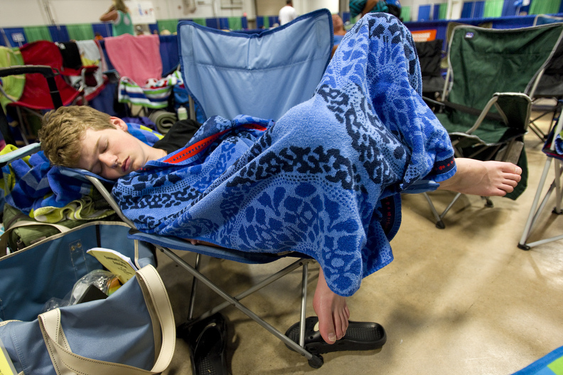 Second Place | Multiple PhotosJerry Wolford, News & RecordOrcas' swimmer Jake Apple, 14,  sleeps in a camp chair after a morning of competition.